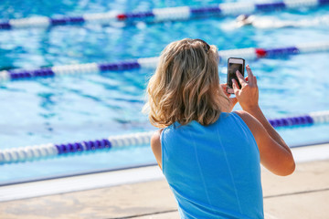 Mother taking pictures with her phone at a swim meet