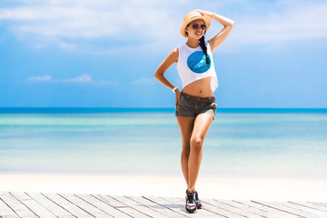 beautiful girl traveler on the blue sea shore, wearing shorts t-shirt thatch hat and sunglasses. concept of summer holiday