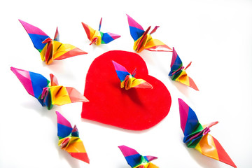 Rainbow origami bird on heart shape sign of freedom, Gay conceptual images