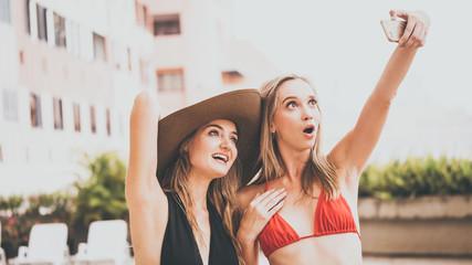 Two beautiful girls having fun taking selfie photo with smart phone camera at swimming pool