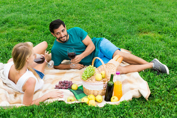 Smiling couple is lying with wineglasses and talking
