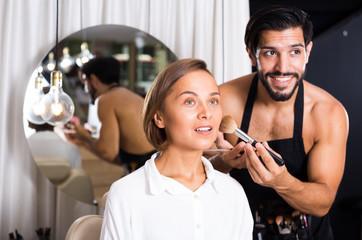 Cheerful male makeup artist applying cosmetics