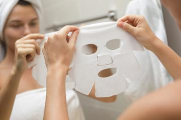 Woman in bathroom is applying facial sheet mask