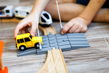 a boy playing with a wooden toy set with cars, modern train, rail road and railway crossing