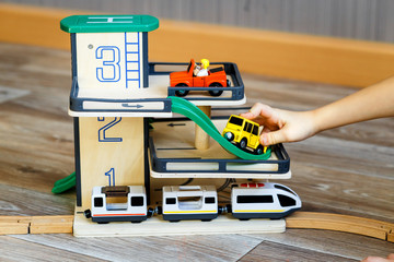 a boy playing with a wooden toy set with cars, modern train, rail road and multi-level parking