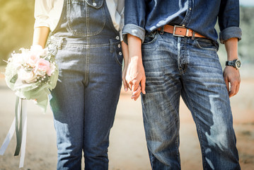 Young loving couple holding hands each other with wedding bouquet flowers , Bride and groom in vintage jeans standing together in soft light of sunset