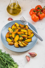 Fried potatoes in a plate. Baby potatoes, green, tomatoes and garlic on the table