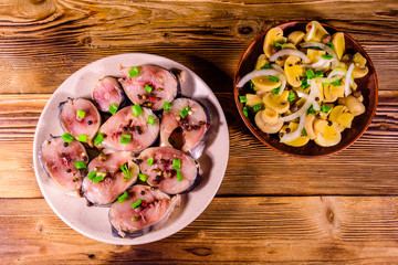 Sliced scomber fish and canned mushrooms with green onion on a ceramic plates on wooden table