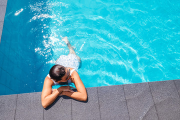 Woman swim in swimming pool at sunny day