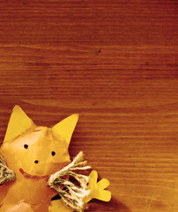 Handmade orange toy cat on red-brown wooden background as template for greeting card or postcard. Top view image with copy space for text.