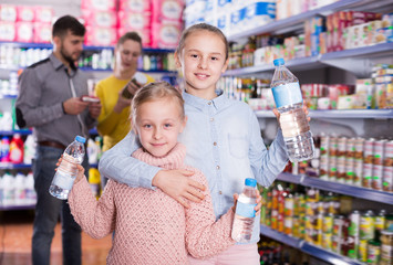 Two small sisters holding bottled water