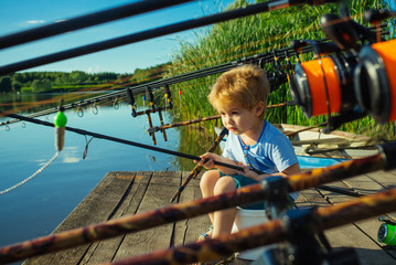 Adorable baby on river with fishing rod