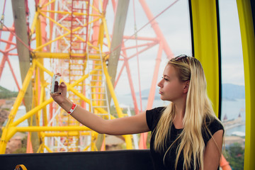Young fashion girl take selfie on the ferris wheel