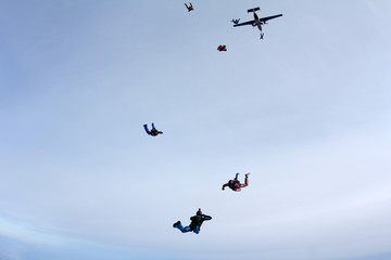 Skydivers are jumping out of a plane.