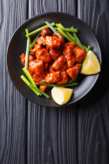 Indian chicken 65 with sauce and green onions and lemon close-up on the table. Vertical top view