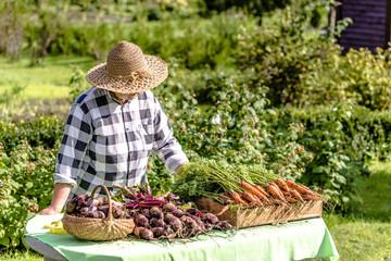 Fresh organic vegetables on farmer market, woman selling produce, local farming concept