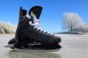 Black hockey skates on a ice rink.
