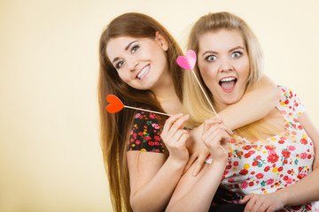 Two happy women holding heart on stick