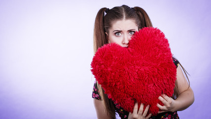 Scared woman holding heart shaped pillow