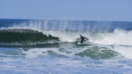 Guy surfing in winter on irish coast