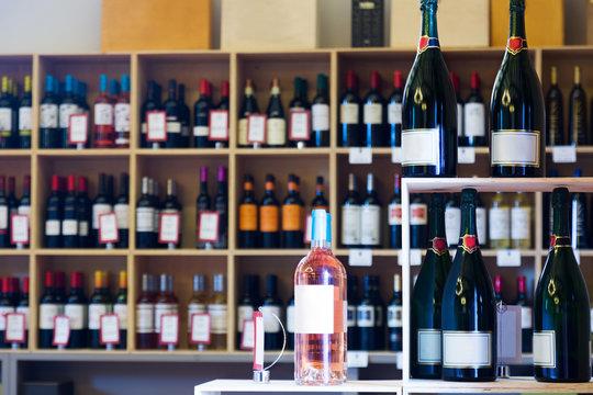 Many wine bottles in shelves of winery shop