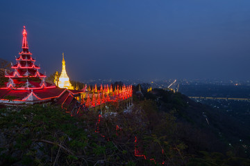 Panoramic view of lit pavilion and golden stupa at the Mandalay Hill and the city below in Mandalay, Myanmar (Burma) in the evening. Copy space.
