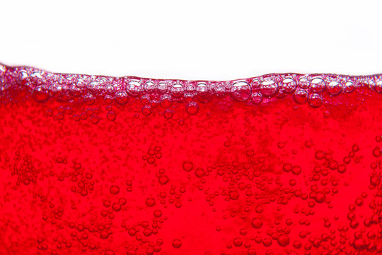 red soda water splashing  with bubbles close up and Dew Point on glass