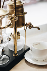 cup of delicious coffee and retro style coffee machine, closeup