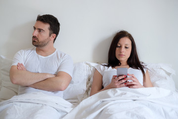 Bored couple and worried man by his wife mobile phone addiction