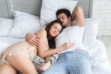 young couple in pajamas sleeping in bed together