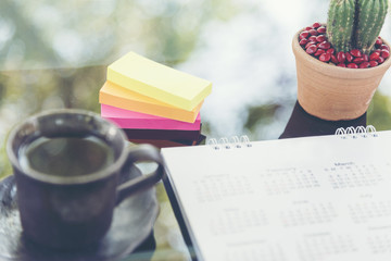 Calendar 2018 Appointments Schedule place on grass table with bohkeh and light on background. colorful post-it and cup of coffee for planner.