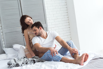 young couple in pajamas resting on bed together  at home