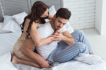 young woman in pajamas hugging boyfriend on bed at home