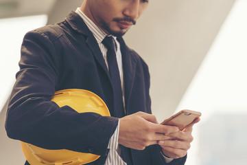 Muslim engineer using smart phone and holding yellow helmet. Construction concept.
