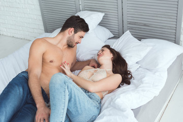 sexy young couple in jeans looking at each other while lying on bed