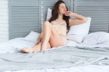 selective focus of young woman in pajamas resting on bed