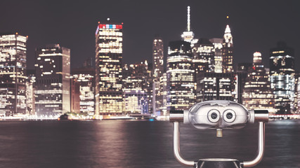Vintage toned picture of binoculars pointed at New York City skyline at night, urban travel concept, selective focus, USA.