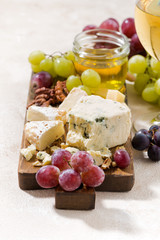 cheeseboard, grapes and wine on a white background, vertical
