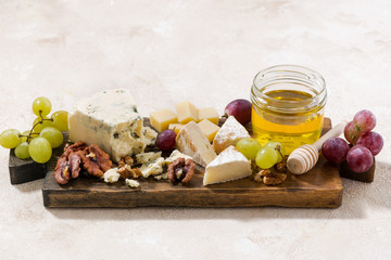 cheeseboard, grapes and honey on a white background, top view