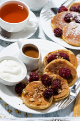 sweet corn pancakes with berries and caramel sauce on white table, top view