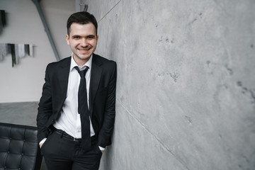 Portrait of a young attractive man in a black suit and tie with a smile and confident look against a gray wall background in a trendy loft style.