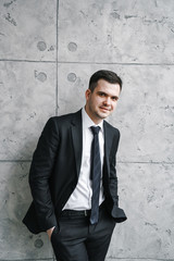 young man in a black suit and tie stands near a gray loft-style wall and looks at the camera. Biznesportret successful freelancer.