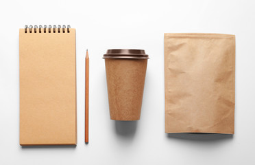 Composition with blank cup, paper package and notebook as mockups for branding on white background