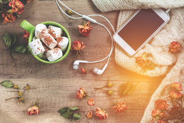Cup of hot chocolate with marshmallow, white knitting wool, dried roses flowers, mobile phone and headphones
