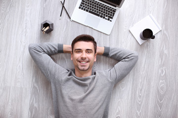 Young man with laptop lying on floor, top view