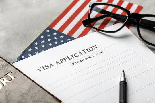 Passport, American flag and visa application form on table. Immigration to USA