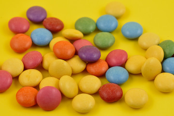 Colorful lentils stock images. Colorful candies on a yellow background. Chocolate lentils snack