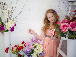 Beautiful girl 10 years old with red hair in the studio with flowers