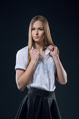 Beautiful smiling teen girl in black skirt and white shirt studio portrait. Happy student or schoolgirl with long hair looking at camera on black background.