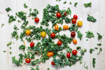 Chopped green kale with red and yellow plum cherry tomatoes on wood background
